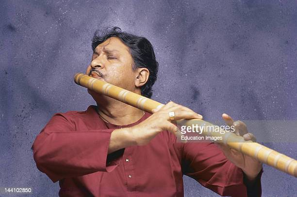Portrait Of Indian Classical Musician Playing Musical Instrument Bansuri Or Flute Made From Hollow Bamboo In Concert India