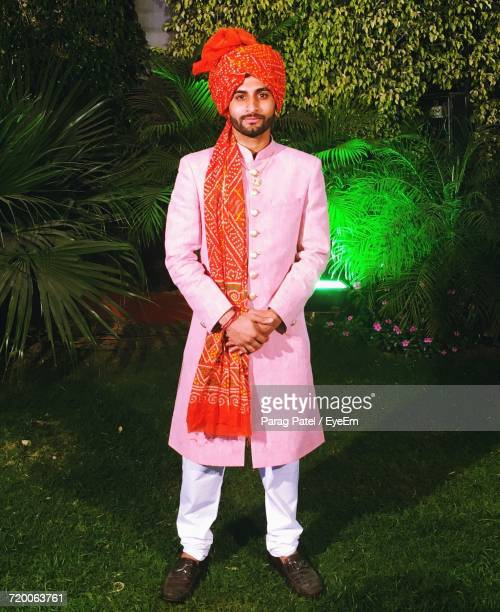 portrait of indian groom standing in lawn at night - 民族衣装 ストックフォトと画像