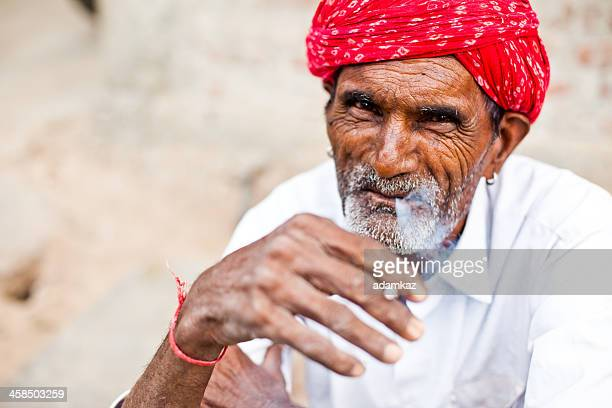 portrait of indian man smoking wearing red turban - vendor stock pictures, royalty-free photos & images