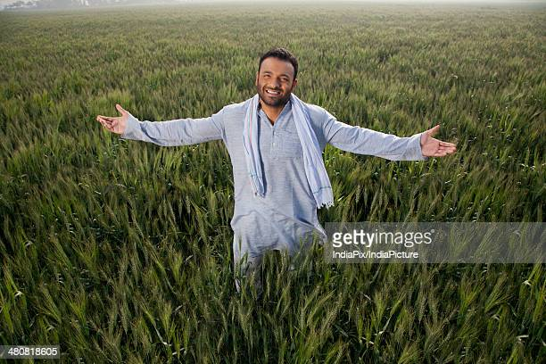 Portrait of Indian man with arms outstretched standing on field