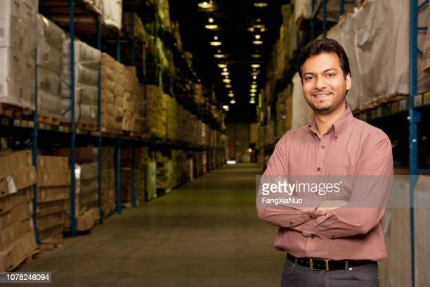 portrait of indian man working in shipping warehouse - indian ethnicity stock pictures, royalty-free photos & images