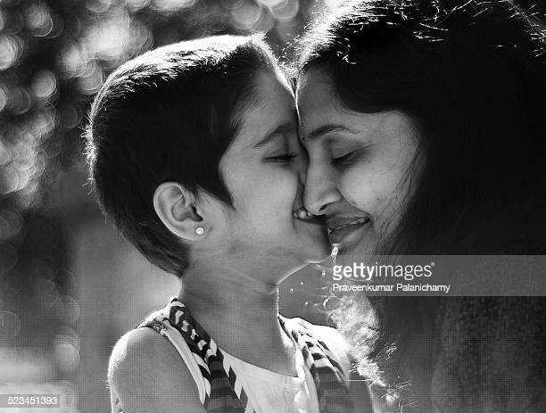 portrait of indian mom and child playing - indian girl kissing stock photos and pictures