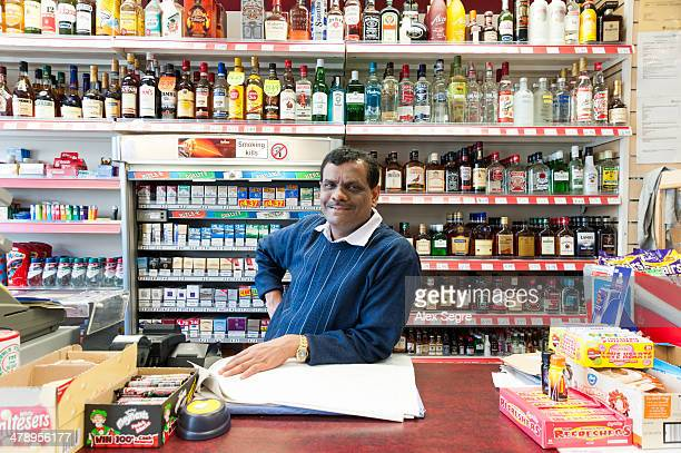 Portrait of Indian offlicence owner inside his corner shop London UK