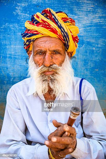 Portrait of Indian old man with smoking pipe