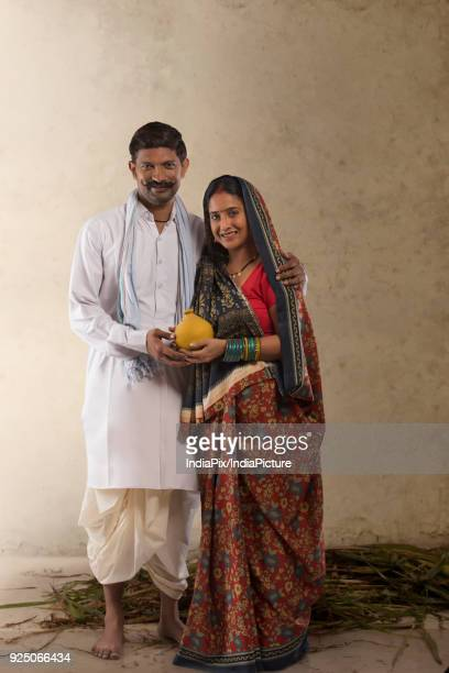 Portrait of Indian rural couple holding clay piggy bank