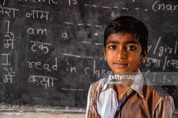 portrait of indian schoolboy in classroom - english language stock pictures, royalty-free photos & images