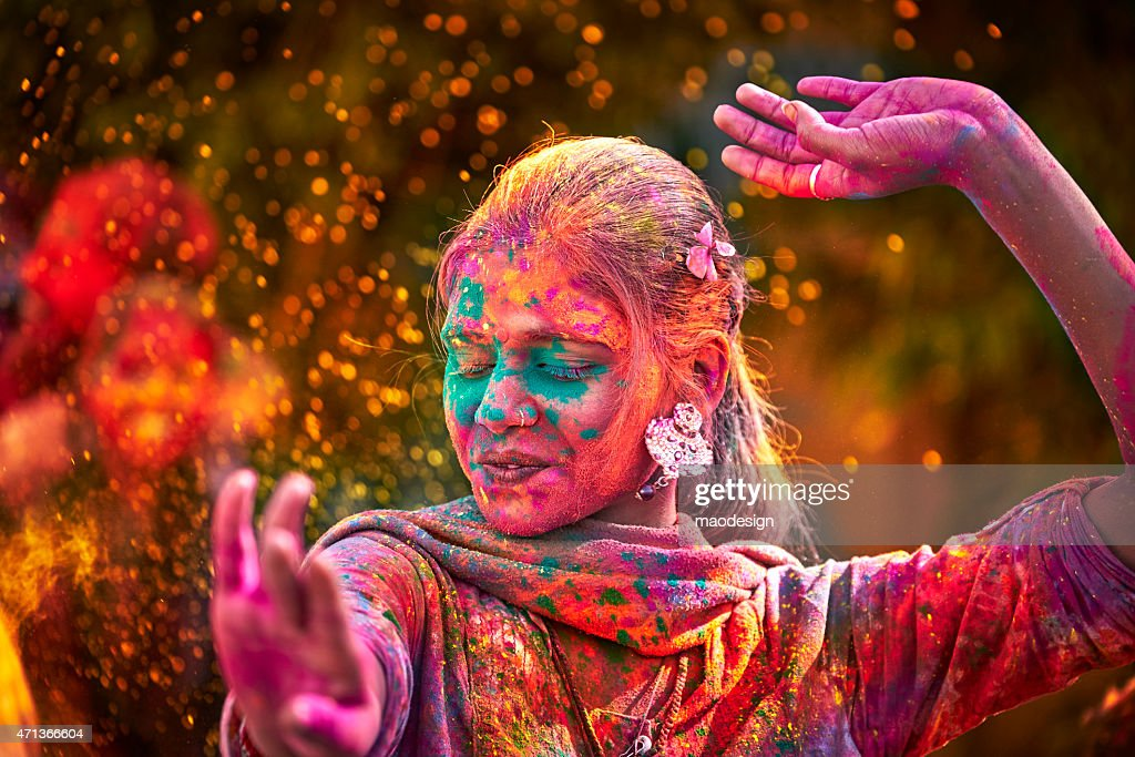 Portrait Of Indian Woman With Colored Face Dancing During Holi : Stock Photo