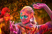 Portrait Of Indian Woman With Colored Face Dancing During Holi