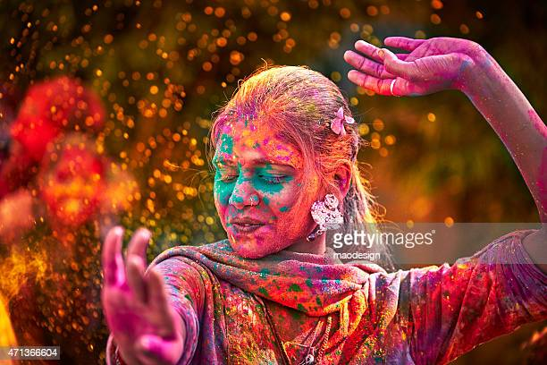 portrait of indian woman with colored face dancing during holi - kleurenfoto stockfoto's en -beelden