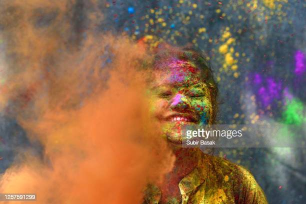 portrait of indian woman with colored face during holi,india. - holi stock pictures, royalty-free photos & images