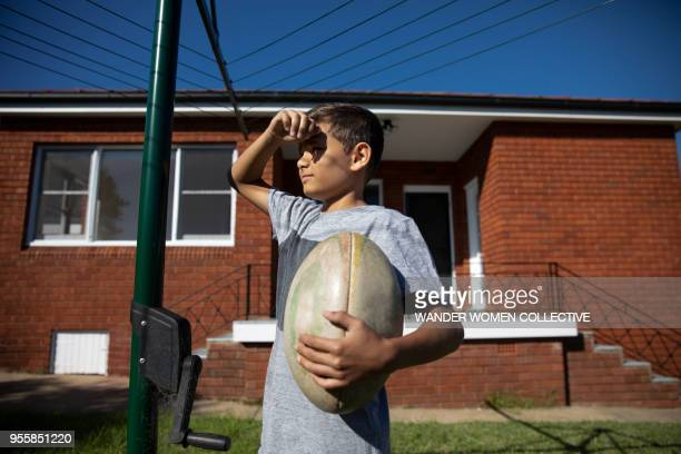 portrait of indigenous australian aboriginal boy under hills hoist holding rugby ball - rugby sport stock pictures, royalty-free photos & images