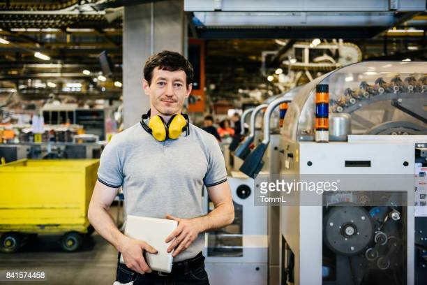 portrait of industrial worker standing in factory - ear protection stock pictures, royalty-free photos & images
