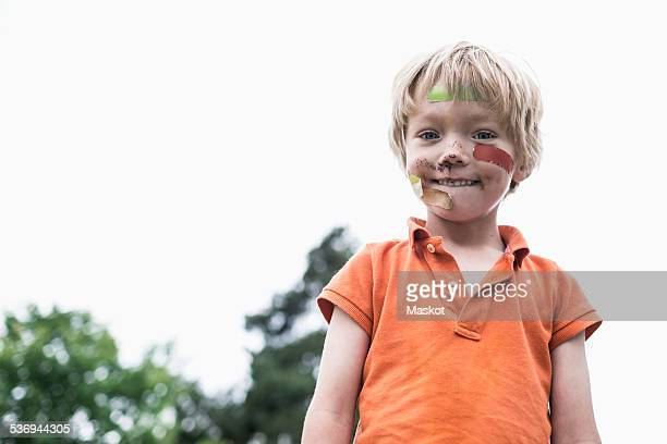 portrait of injured boy standing against clear sky - machucado imagens e fotografias de stock