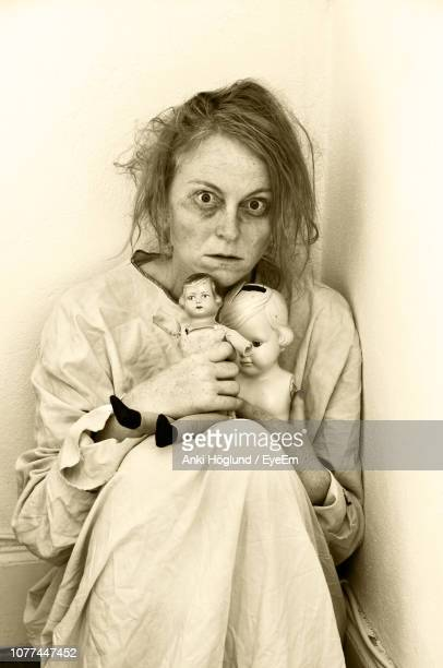 portrait of insane woman with toys sitting against wall at home - insanity stock pictures, royalty-free photos & images