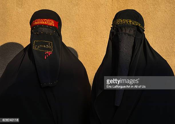 Portrait of iranian shiite muslim women with their faces hidden by a veil mourning Imam Hussein on Tasua during the Chehel Manbar ceremony one day...