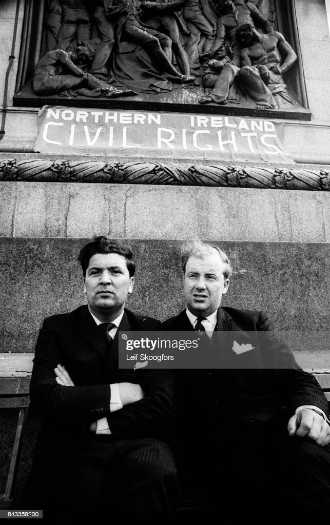 Portrait of Irish politicians (and co-founders of the Social Democratic and Labour Party) John Hume (left) and Ivan Cooper as the pose together at the base of Nelson's Column in Trafalgar Square, under a sign that reads 'Northern Ireland Civil Rights,' London, England, 1970. Hume went on to win a Nobel Peace Prize for his role in various agreements, including the Good Friday Agreement, during the Northern Ireland peace process.