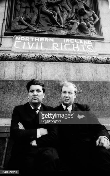Portrait of Irish politicians John Hume and Ivan Cooper as the pose together at the base of Nelson's Column in Trafalgar Square under a sign that...