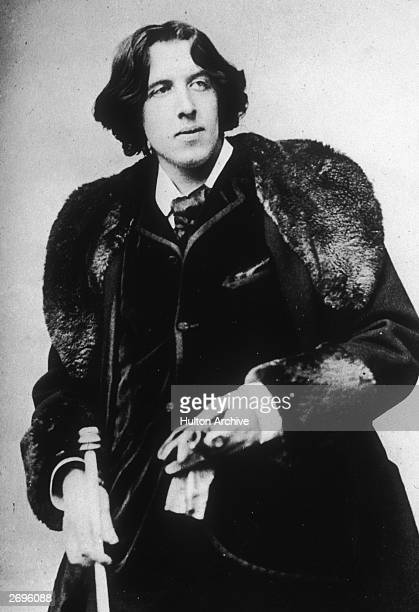 Portrait of Irishborn author and critic Oscar Wilde wearing a fur stole and holding a cane and gloves