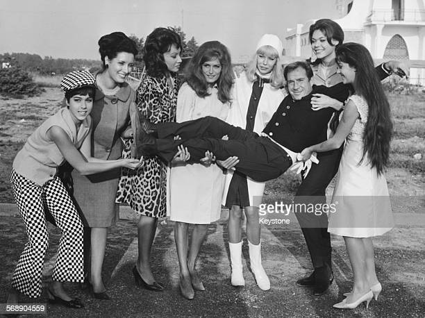 Portrait of Italian actor Ugo Tognazzi being held up by a group of actresses Romina Power Maria Capparelli Maria Grazia Buccella Monica Swers Susanne...