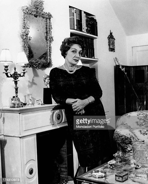 Portrait of Italian actress Andreina Pagnani smiling sitting in a chair in her house Rome 1964