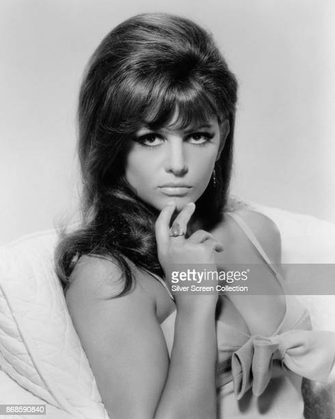 Portrait of Italian actress Claudia Cardinale, in a low-cut dress with a bow, as she poses with two fingers on her chin, 1960s.