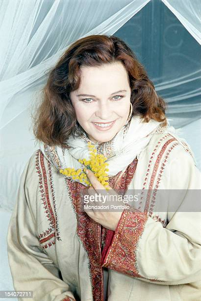 Portrait of Italian actress Laura Antonelli holding a bunch of mimosas 1990