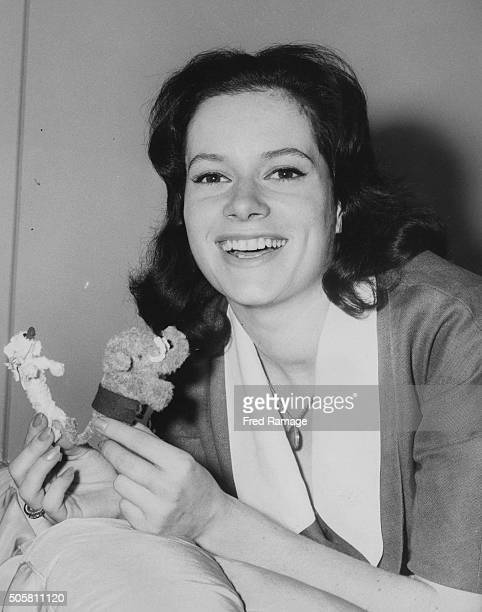 Portrait of Italian actress Luciana Paluzzi holding two small toys, in her hotel room prior to the premiere of her film 'Sea Fury' at the Dorchester...