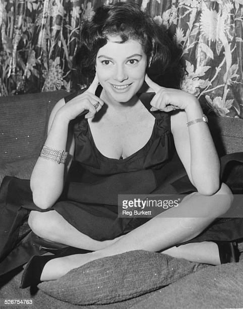 Portrait of Italian actress Luciana Paoluzzi, sitting cross legged on a bed, at the Savoy Hotel, London, January 13th 1958.