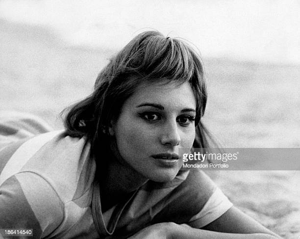 Portrait of Italian actress Paola Pitagora lying on the sand 1963