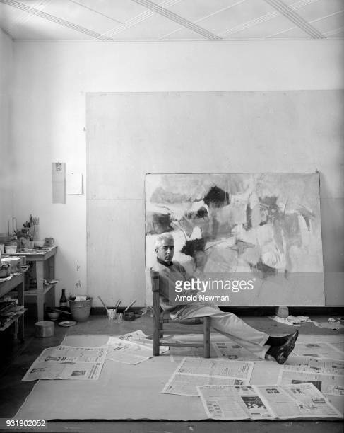 Portrait of Italian artist Afro Basaldella as he sits in front of one of his paintings Rome Italy November 8 1959