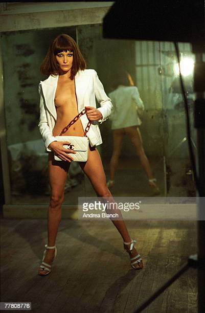 Portrait of Italian fashion model Carla Bruni as she poses, dressed only in an open jacket, high heels, and a strategically placed handbag, as she...