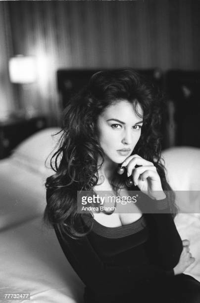 Portrait of Italian film actress and fashion model Monica Bellucci as she sits on the edge of a bed 1996