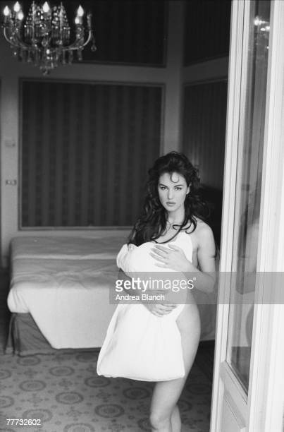 Portrait of Italian film actress and fashion model Monica Bellucci as she stands naked by the door to a bedroom partially covered by a pillow she...
