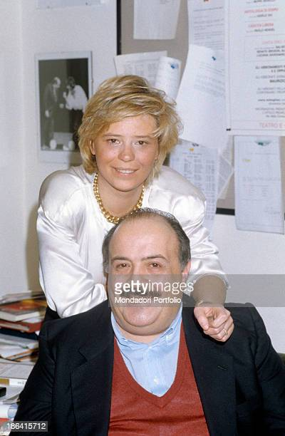 Portrait of Italian journalist and TV host Maurizio Costanzo smiling with his wife and Italian TV presenter Maria De Filippi behind him 1991