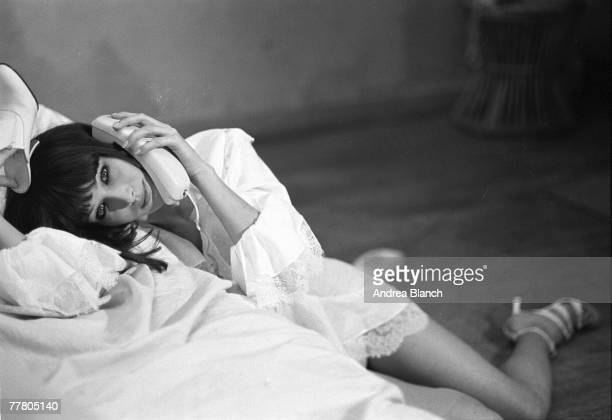 Portrait of Italian model Carla Bruni as she poses for a photo shoot slouched against a bed a shoe in one hand and telephone in the other 1995