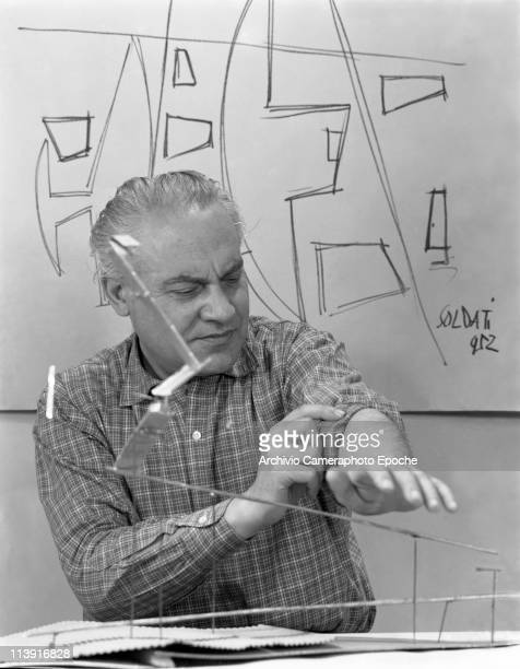 Portrait of Italian Painter Atanasio Soldati sitting between a sculpture and a painting of his rollinup a sleeves of his checked shirt Milan 1952