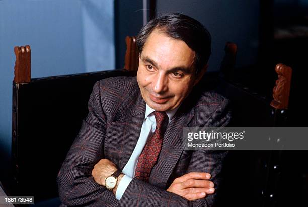 Portrait of italian politician Giuliano Amato Minister of the Treasury in the Goria Cabinet with his arms folded seated at the desk of his office...