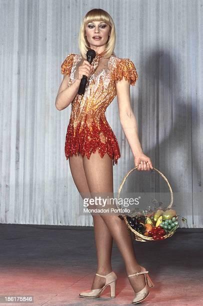 Portrait of Italian showgirl and TV presenter Raffaella Carrà holding a fruit basket in a stage costume in the talk show Pronto Raffaella 1983
