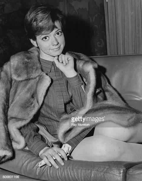 Portrait of Italian singer Rita Pavone wearing a mink coat sitting on the couch in her London hotel room 1966