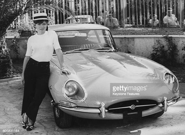 Portrait of Italian singer Rita Pavone wearing a straw boater hat and leaning on the bonnet of a her pink Jaguar car a birthday present from her...