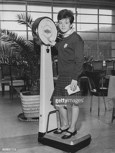Portrait of Italian teenage singer Rita Pavone wearing her school uniform and standing on a set of scales Rome February 1963