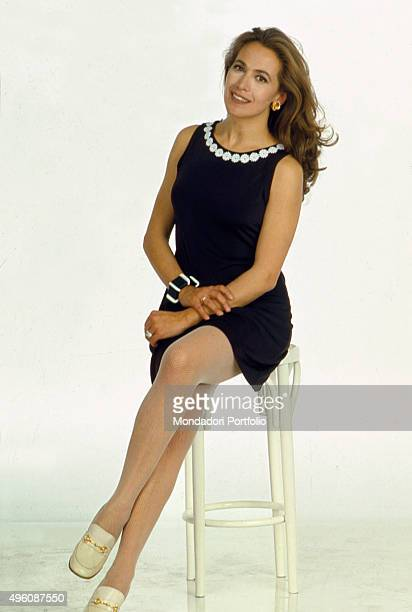 Portrait of Italian television host and actress Barbara D'Urso sitting on a stool posing for a photo shoot inside a television studio Italy 1997