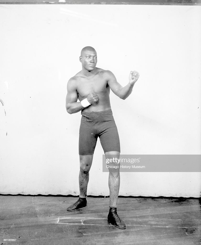 Portrait of Jack Johnson, African American heavyweight champion boxer, standing in an ordinary boxing stance in front of a light colored background in a room in Chicago, IL, 1907. He is wearing boxing trunks and shoes. He has a band of tape on his right wrist. From the Chicago Daily News collection.