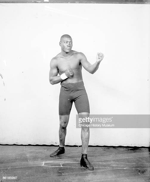Portrait of Jack Johnson African American heavyweight champion boxer standing in an ordinary boxing stance in front of a light colored background in...