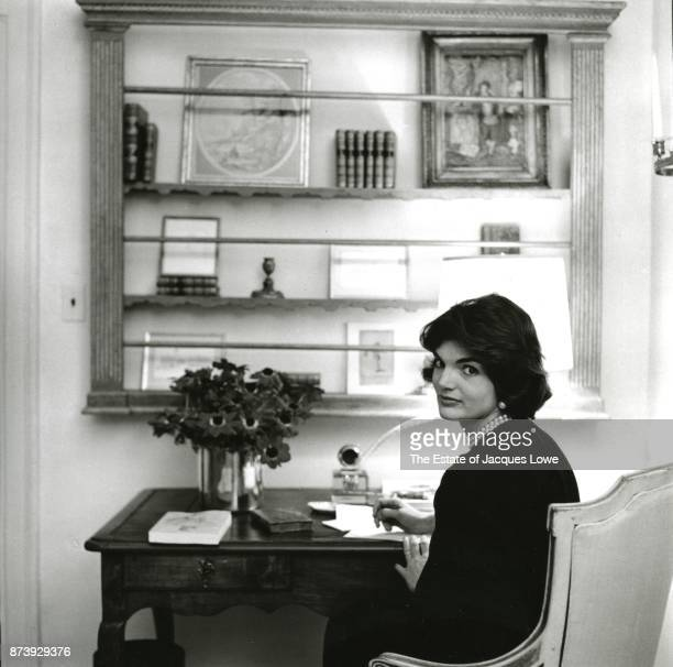 Portrait of Jacqueline Kennedy seated at a desk as she looks over her shoulder in her townhouse in the Georgetown neighborhood Washington DC Fall 1959