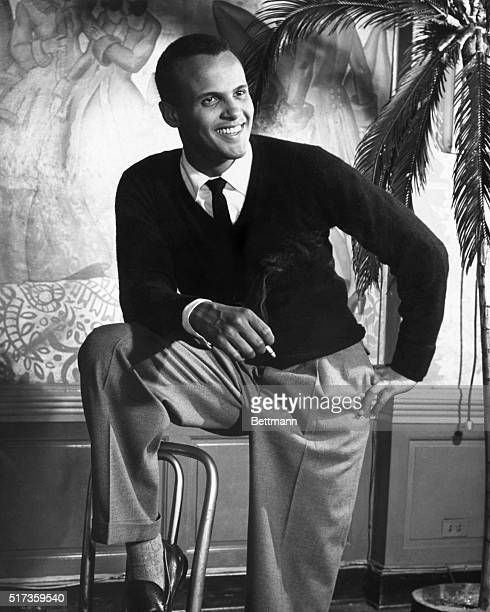 Portrait of Jamaican-American musician, actor, and Civil Rights activist Harry Belafonte as he poses, one foot on a chair and a cigarette in his...