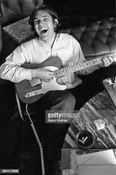 Portrait of Jann Wenner founder and publisher of Rolling Stone magazine playing a Fender Telecaster guitar at home in San Francisco 1969