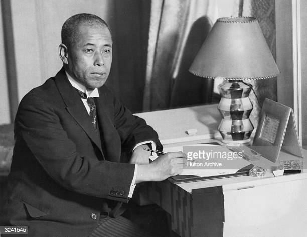Portrait of Japanese admiral Isoroku Yamamoto wearing a suit and tie seated at a desk with a pen in his hand London Yamamoto planned and directed the...