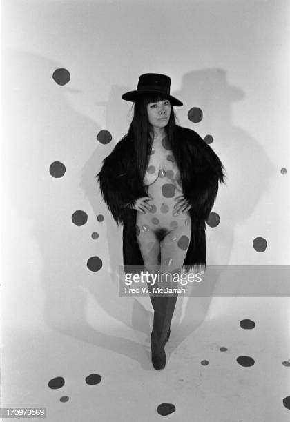 Portrait of Japanese artist Yayoi Kusama as she poses in a Bolero hat and boots completely naked under a fur coat her body painted with polka dots...