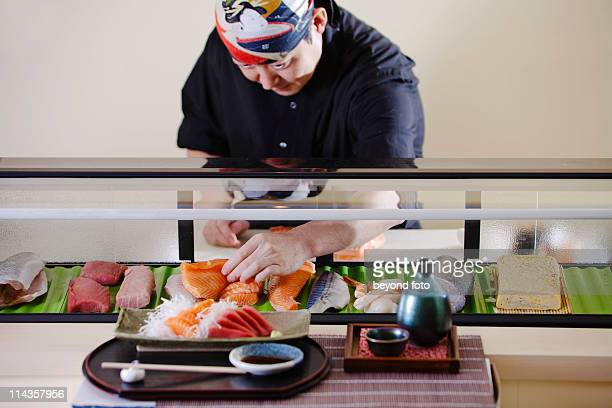 portrait of japanese chef in arranging sushi in restaurant